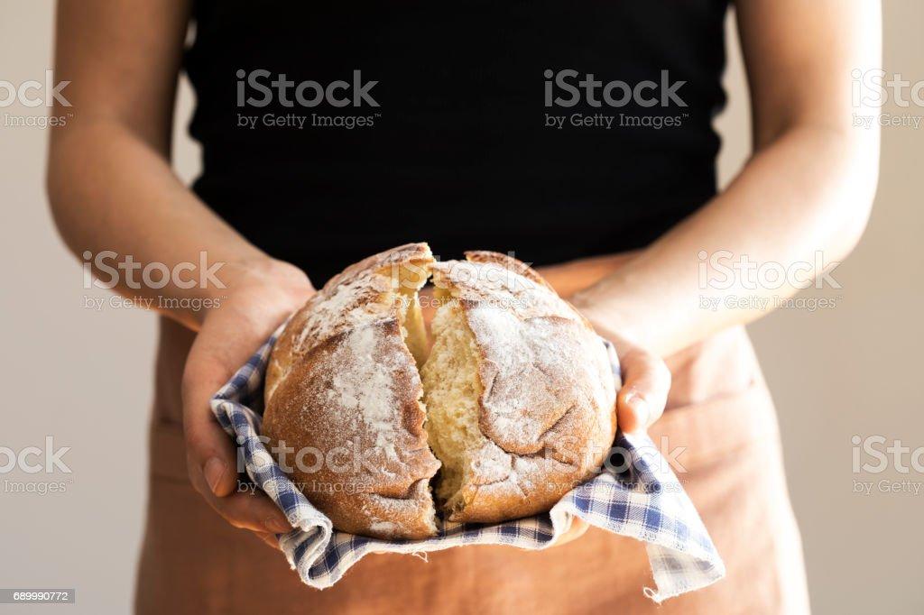 Female hand holding hot freshly baked bread stock photo