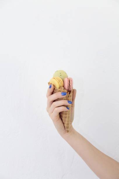 female hand holding ice cream cone with macaroons. - nails ice cream imagens e fotografias de stock