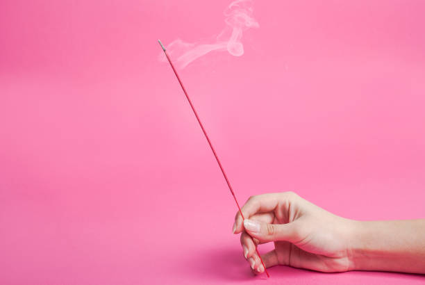 Female hand holding incense sticks that smokes isolated on pink background Young Female hand holding incense sticks that smokes isolated on pink background. Close up. incense stock pictures, royalty-free photos & images