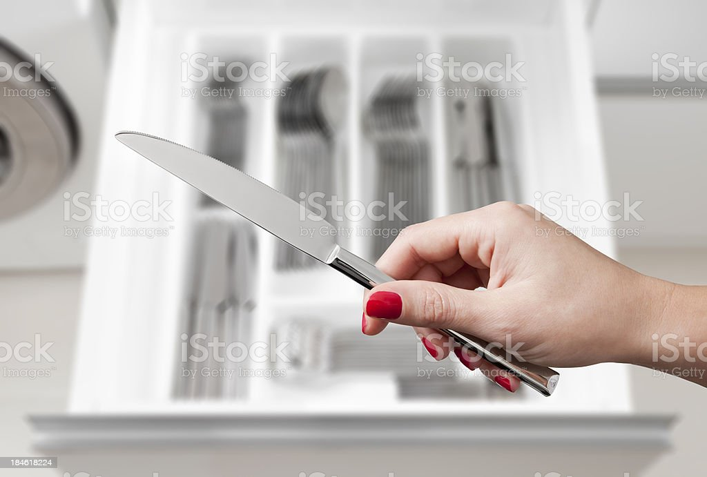 female hand holding knife over silverware drawer royalty-free stock photo