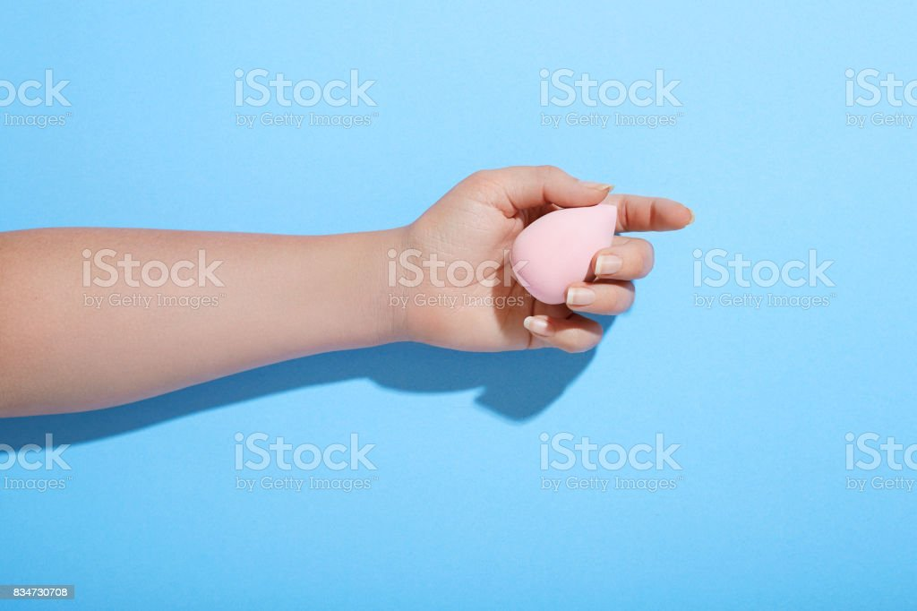 Female hand holding make-up sponge on saturated blue background stock photo