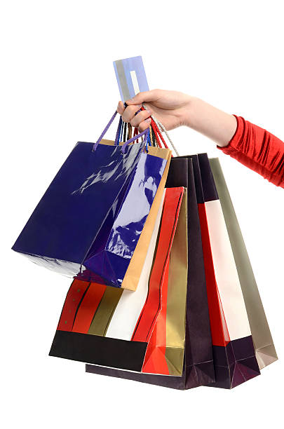 Female hand holding many shopping bags and a credit card. stock photo
