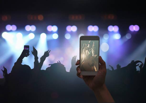 weibliche hand, die mobile smart telefon mit video-aufzeichnung oder live-stream der konzert-masse mit superstar songer und silhouetten von musik fanclub mit hand aktion anzeigen, musical und konzert-konzept - bandanzeige stock-fotos und bilder