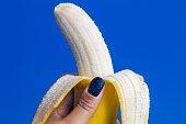 Female Hand Holding Peeled Yellow Banana on Blue Background