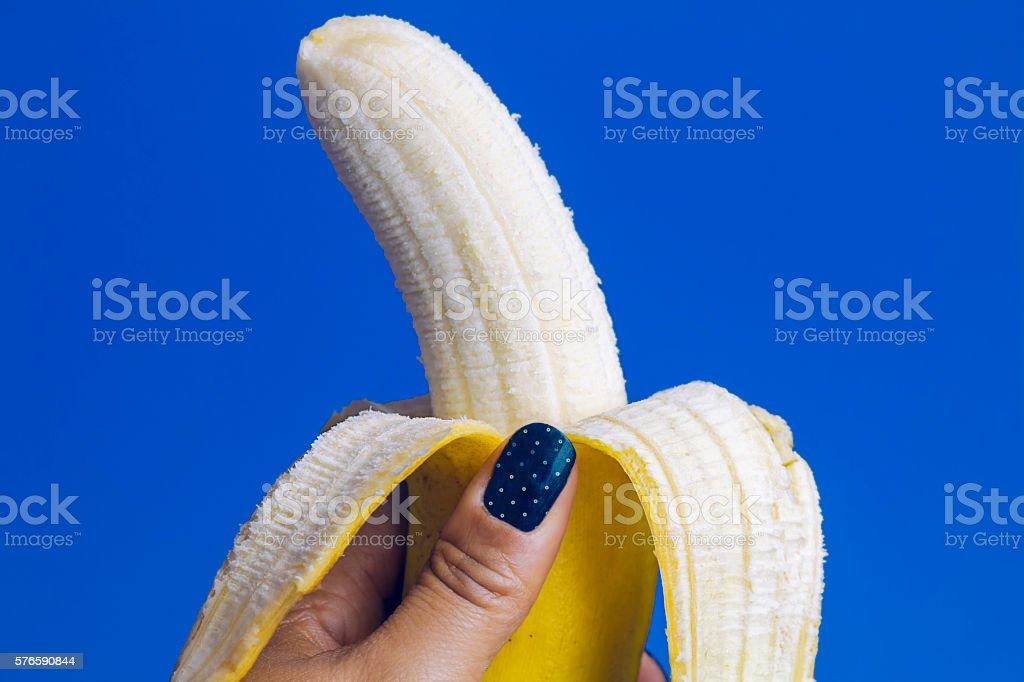 Female Hand Holding Peeled Yellow Banana on Blue Background foto