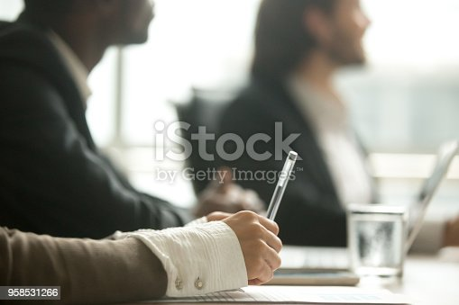 istock Female hand holding pen making notes at meeting, closeup view 958531266
