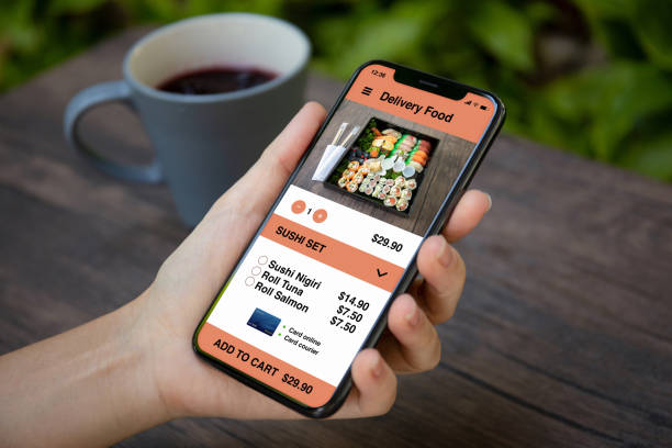 female hand holding phone with app for delivery sushi food - food delivery стоковые фото и изображения