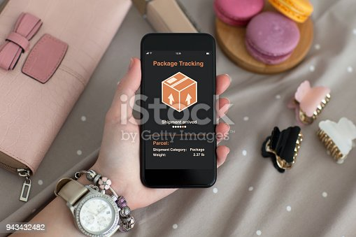istock female hand holding phone with app tracking delivery package 943432482