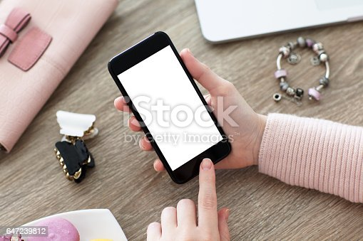 936543982istockphoto female hand holding phone with isolated screen on table 647239812