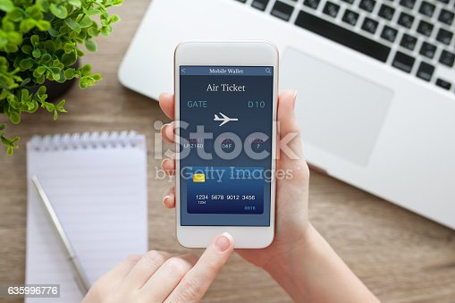 istock female hand holding phone with online air ticket and notebook 635996776