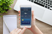 female hand holding white phone with online air ticket and notebook