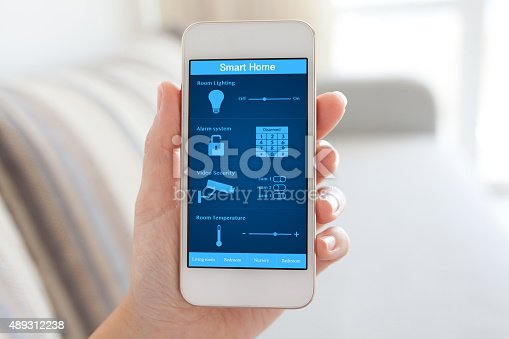 istock female hand holding phone with smart home on the screen 489312238