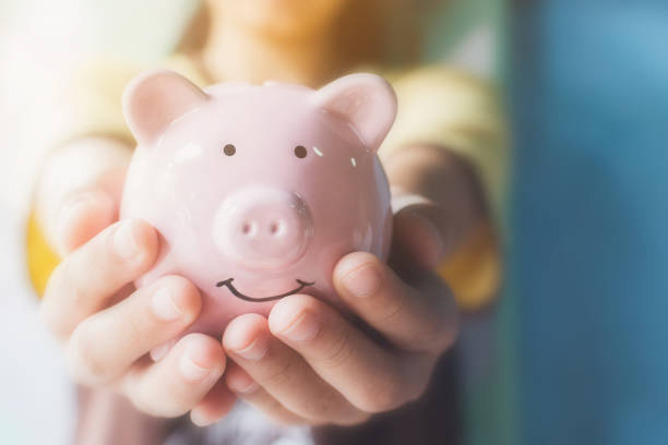 Female hand holding piggy bank. Save money and financial investment stock photo