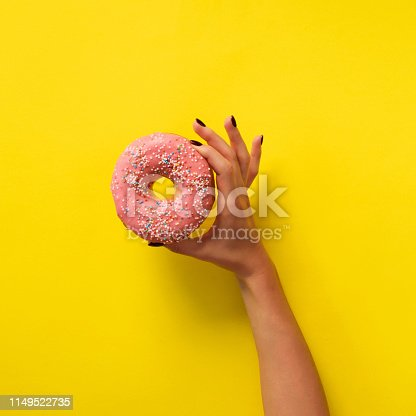 Female hand holding pink donut over yellow background. Top view, flat lay. Sweet, dessert, diet concept. Banner with copy space. Weight lost after holidays.