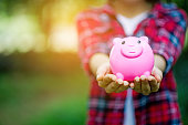 istock Female hand holding pink piggy bank, piggy bank and happy with savings. And copy space 1069015918