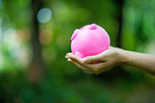 istock Female hand holding pink piggy bank, piggy bank and happy with savings. And copy space 1069015938