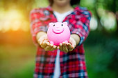 istock Female hand holding pink piggy bank, piggy bank and happy with savings. And copy space 1069015952