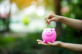 istock Female hand holding pink piggy bank, piggy bank and happy with savings. And copy space 1069015964