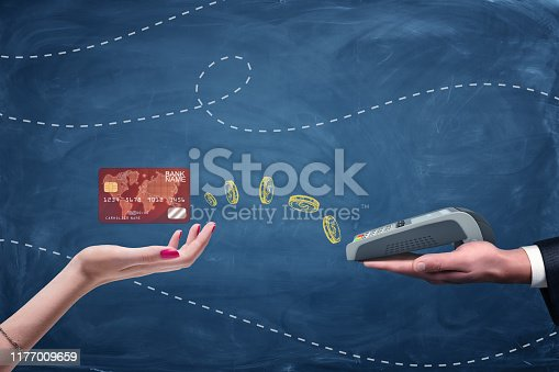 945598452 istock photo Female hand holding plastic card and male hand holding pin pad on blue background. 1177009659