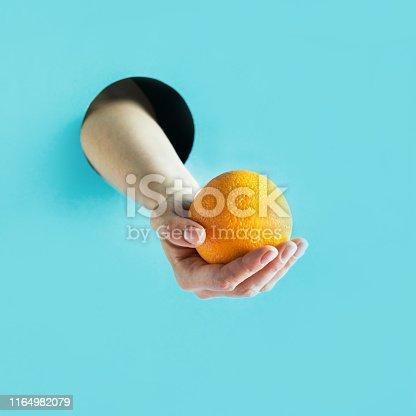 istock Female hand holding ripe orange in paper hole. 1164982079