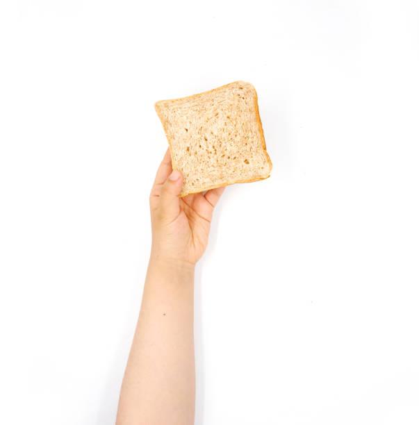Mão fêmea que prende o pão cortado em um fundo branco - foto de acervo