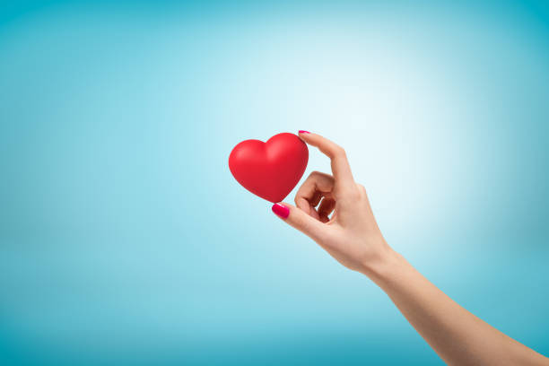 Female hand holding small red heart between fingers on light blue background.