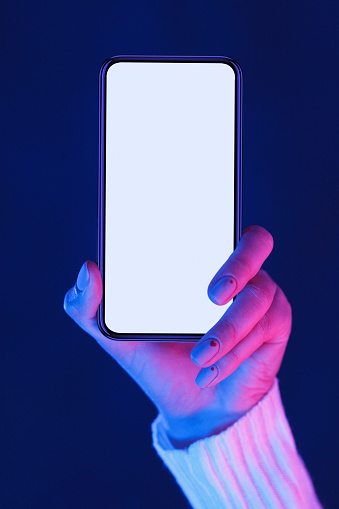 istock Female hand holding smartphone with blank screen in neon lights 1198232355