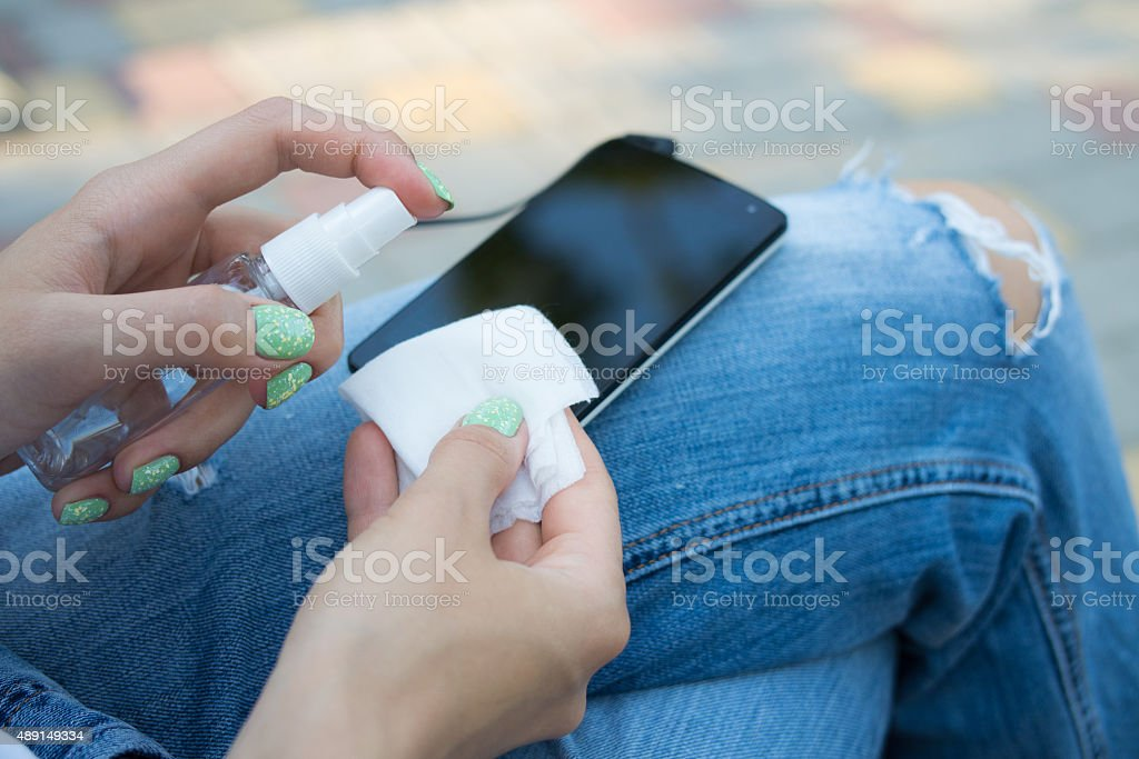 Female hand holding spray and cloth for cleaning the phone stock photo