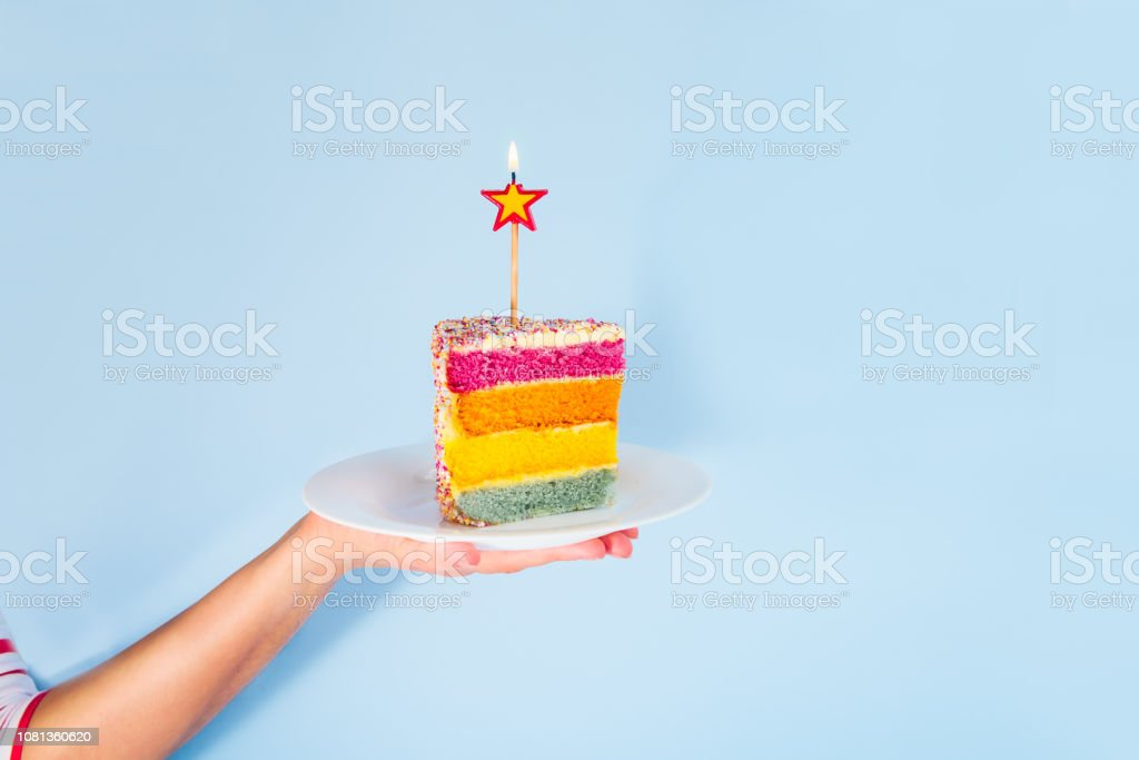 Female hand holding white plate with slice of Rainbow cake with birning candle in the shape of star isolated on blue background. Happy bithday, party concept. Square card. Selective focus. Copy space. stock photo