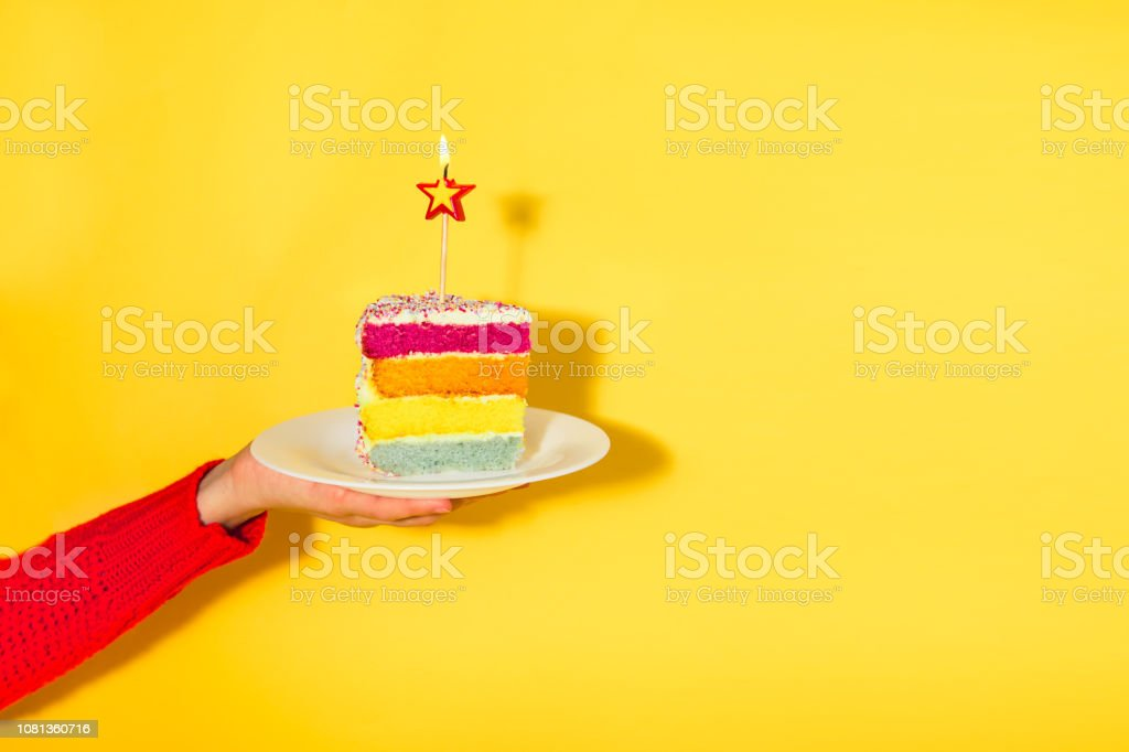 Female hand holding white plate with slice of Rainbow cake with birning candle in the shape of star isolated on yellow background. Happy bithday, party concept. Selective focus. Copy space. stock photo