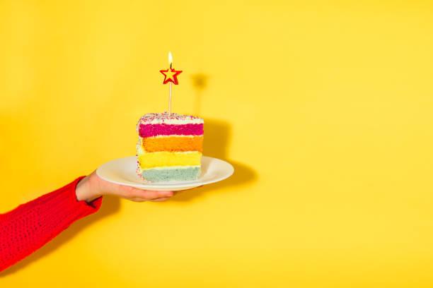weibliche hand mit weißen teller mit regenbogen kuchen mit birning kerze in der form eines sterns auf gelbem hintergrund isoliert. happy bithday, party konzept. selektiven fokus. kopieren sie raum. - einladungskarten kindergeburtstag stock-fotos und bilder