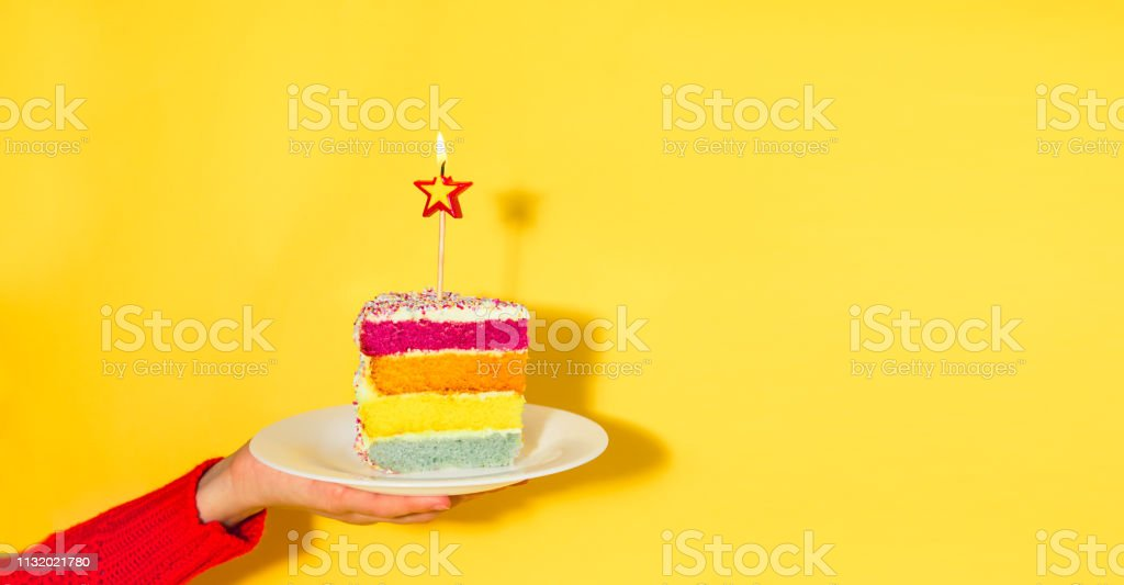 Female hand holding white plate with slice of Rainbow cake with birning candle in the shape of star isolated on yellow background. Happy bithday, party concept. Wide banner. Copy space. stock photo
