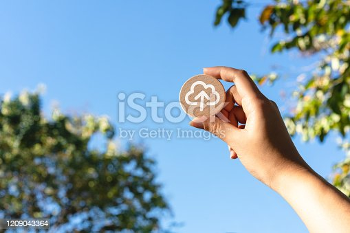 istock Female hand holding wood disc with cloud computing symbol up to a blue sky 1209043364
