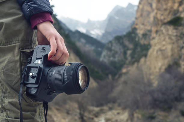 A female hand holds a camera against a mountain landscape stock photo