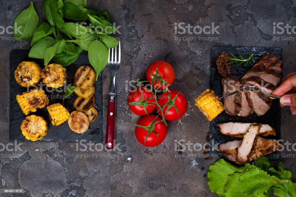 female hand holds a fork with grilled corn on the background fresh three types of grilled steak on slate plate with spinach, tomato and grilled potatoes royalty-free stock photo