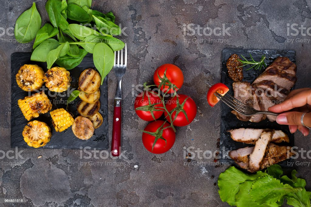 female hand holds a fork with slice tomato on the background fresh three types of grilled steak on slate plate with spinach, tomato and grilled potatoes royalty-free stock photo