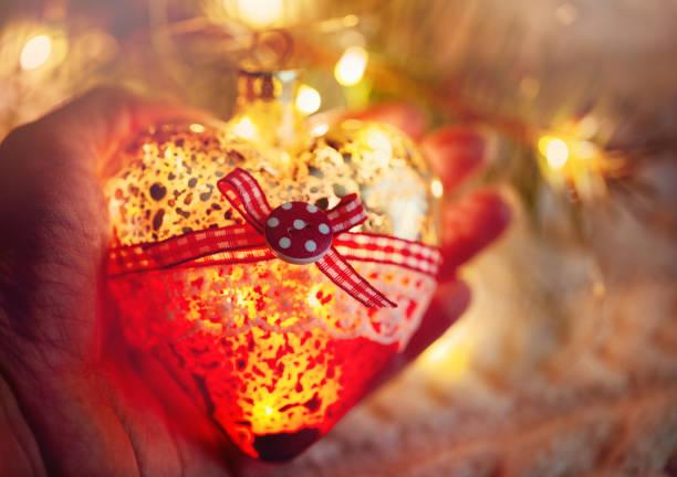 weibliche hand hält ein glas heart, weihnachtsspielzeug - ein kranz in den händen auf dem hintergrund der warme strickpullover. abendzeit. in rottönen - weihnachtsspende stock-fotos und bilder