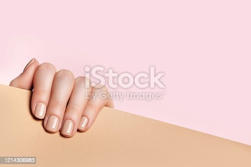 Female hand holds a sheet of paper and demonstrates a nude manicure. Pink, beige background with place for text.
