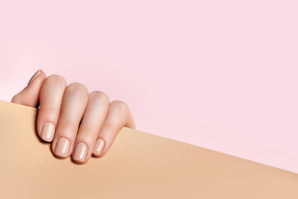 Female hand holds a sheet of paper and demonstrates a nude manicure Female hand holds a sheet of paper and demonstrates a nude manicure. Pink, beige background with place for text. nude women pics stock pictures, royalty-free photos & images