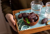 A female hand holds a tray with dates, and water and a rosary - hthe things used to break the fast at sunset during the Muslim holy month of Ramadan. Selective focus, place for text.