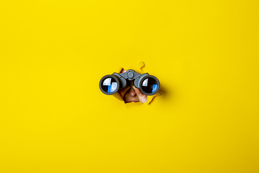 Female hand holds black binoculars on a yellow background. Journey, find and search concept.
