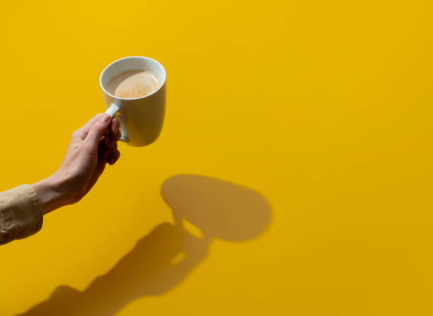Female hand holds cup of coffee on yellow background stock photo