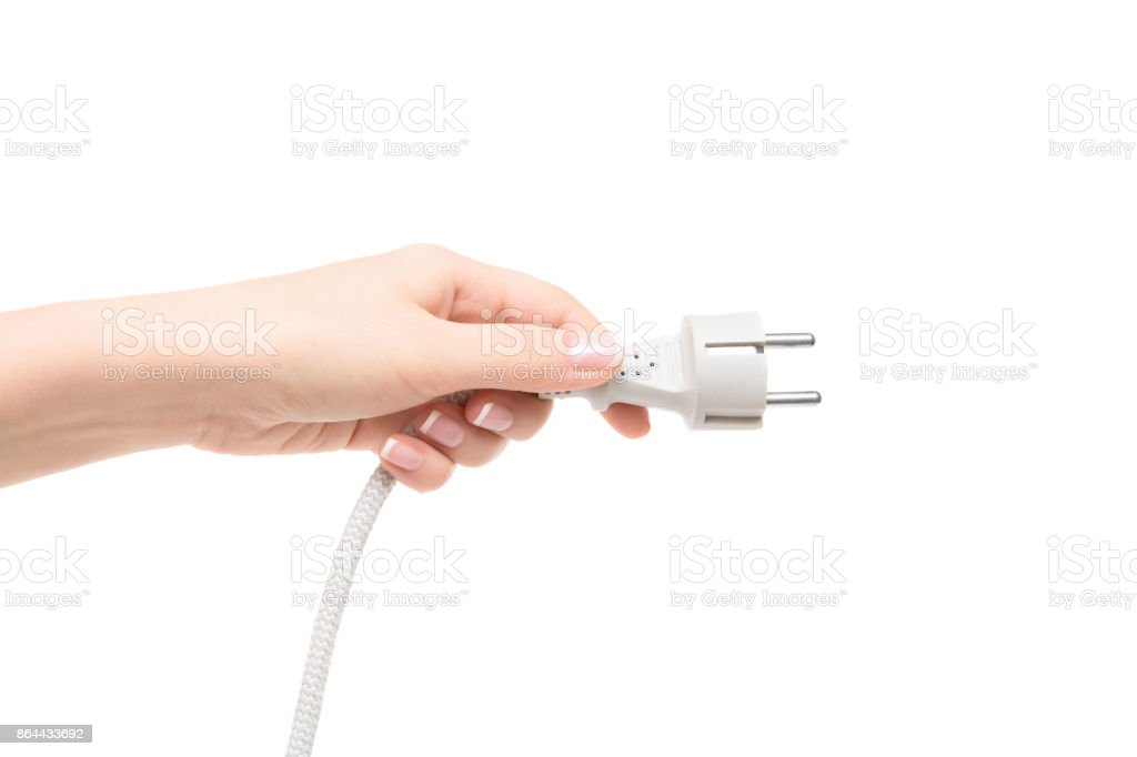 Female hand holds electric plug on a white background. stock photo