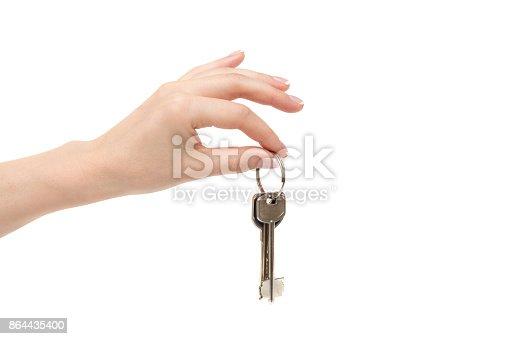 istock Female hand holds keys on white background. 864435400