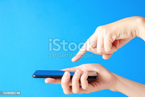 istock Female hand holds smartphone on blue background. Woman touch mobile display with finger 1048065748