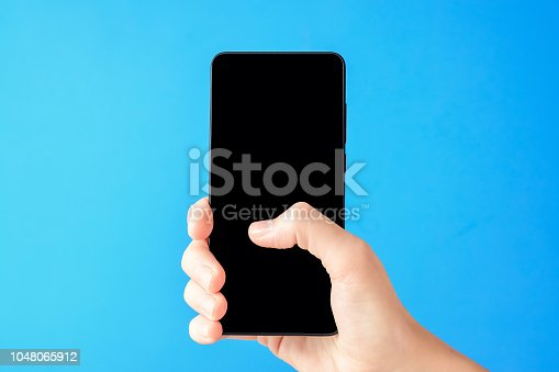 istock Female hand holds smartphone on blue background. Woman touch mobile display with finger 1048065912