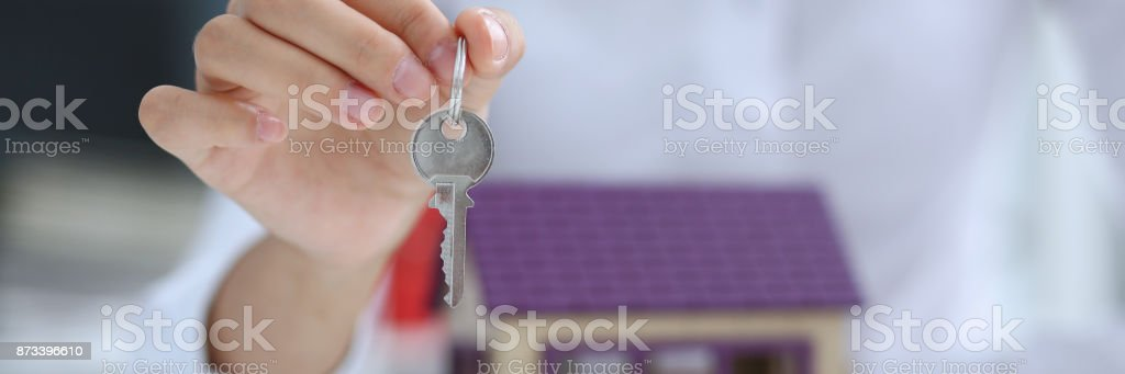 Female hand holds the key to the lock in the hand stock photo