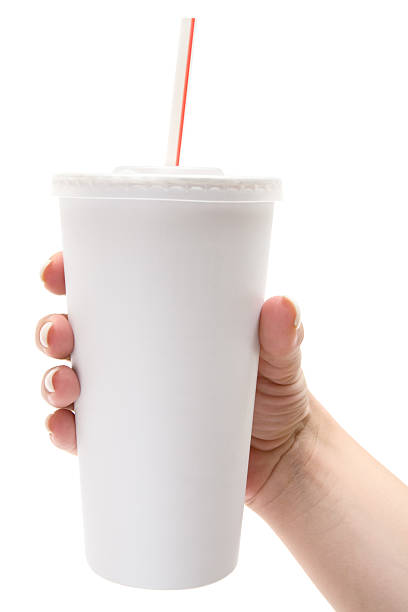 Female hand holds white disposable cup stock photo
