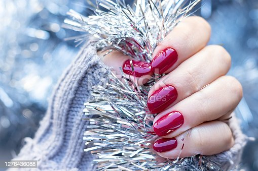 Female hand in a gray knitted sweater with a beautiful glossy manicure - burgundy, dark red, cherry color nails on background of silver Christmas tinsel garland. Selective focus. Closeup view