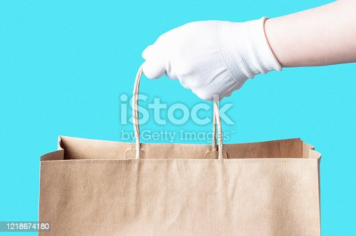 Female hand in a white glove holds a brown cardboard bag, food delivery concept.